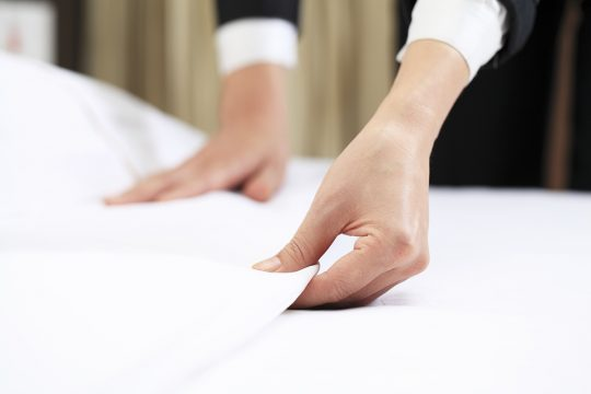 Close-up of a maid's hands making bed in a hotel room.