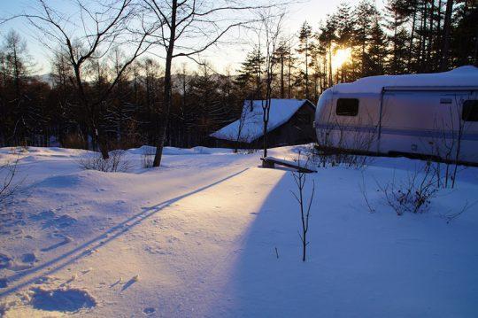 冬の積雪の後の夕暮れ。我が家の庭も、雪のベールで包まれる。