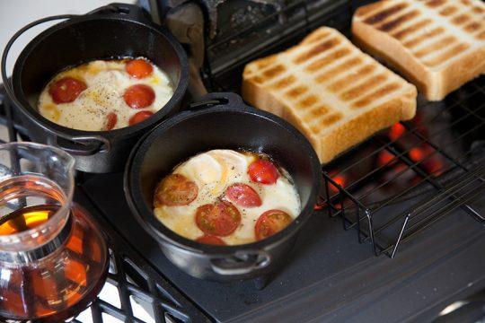 薪ストーブはバーモントキャスティングス製「アンコール」。燃焼効率も良くストーブクッキングを得意とします。朝食メニューは炉内をオーブン代わりにした卵のココット。ストーブトップを開け直火でトーストやお餅も焼ける。
