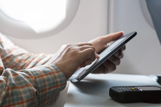 Hands of man browsing gadget in aircraft