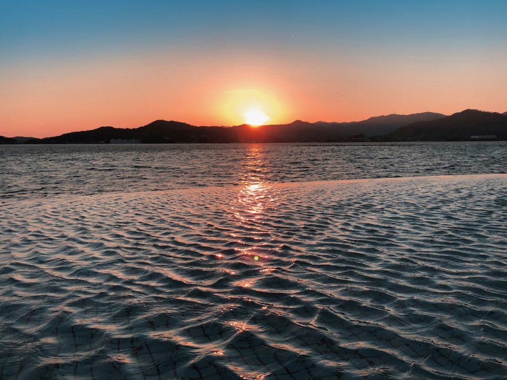 こちらは浜名湖の向こうに沈む夕陽。茜色の光を受けて濃紺の湖面の波形が複雑な色合いを生み出しています